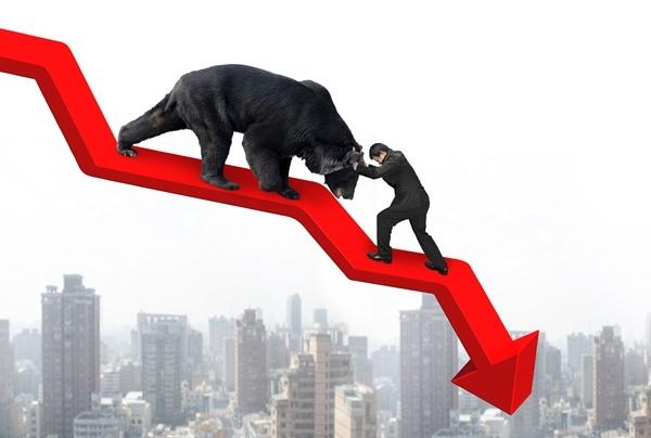obchodník proti černému medvědu na červené šipce v klesající trendu na pozadí velkoměsta. Koncept investora bojujícího s medvědím trendem