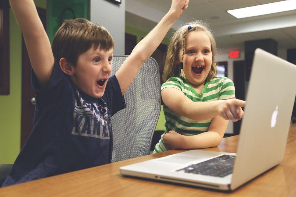 dvě děti se radují z výhry v počítačové hře