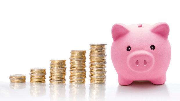 postupně rostoucí komínky mincí a růžová kasička ve tvaru prasátka