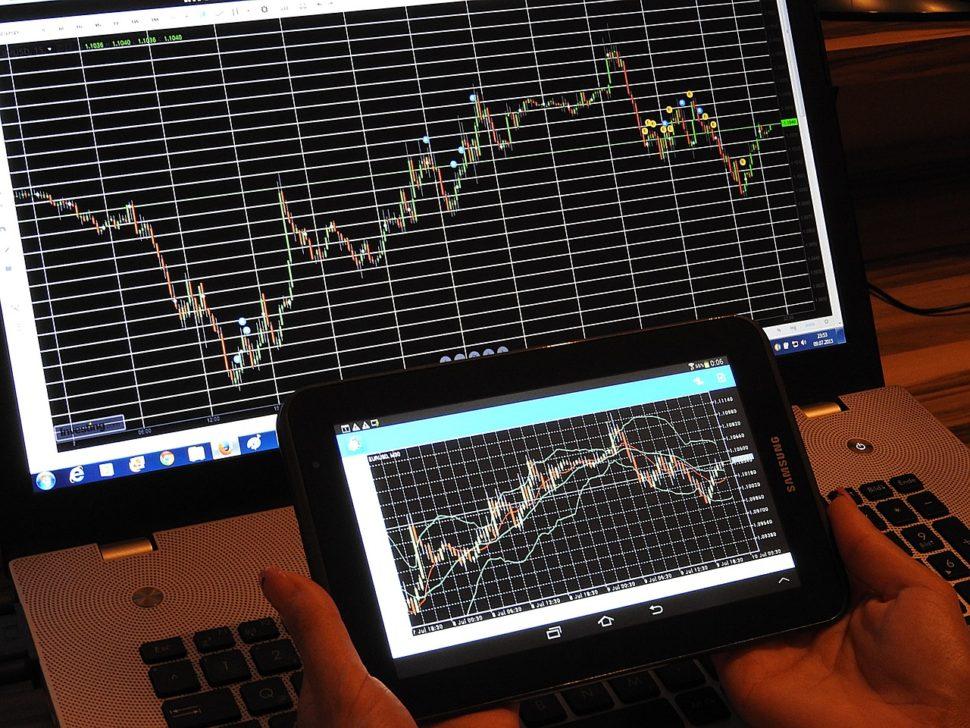 člověk koukající na vývoj forexového trhu na počítači a tabletu