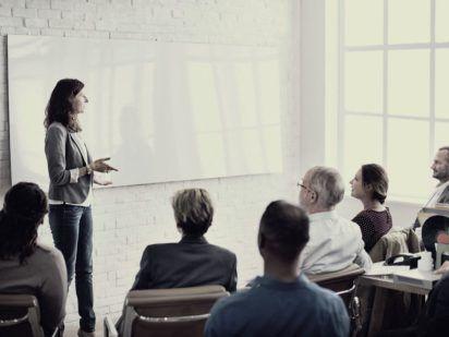 Paní přednášející skupině lidí ve třídě